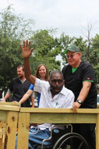 Claude Adams waves to neighbors as Ken Whitaker of Legend Healthcare helps him up his new ramp. Kelly Wickersham, OTA of Legend, and April Wilson, RN, BSN, of CIMA Hospice, celebrate his homecoming Sunday.